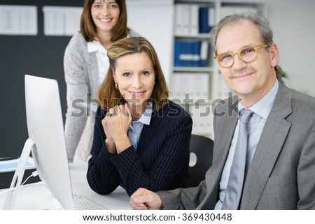 Motivated successful business manageress working with two co-workers, a man and woman, at a desktop computer, focus to her in the center
