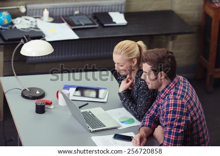 Motivated team at work in the office with a young businessman and woman sitting at a desk smiling as they read information on a laptop together, high angle view - stock photo