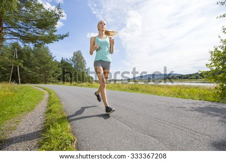 Motivated woman runs fast on a road in the forest - stock photo