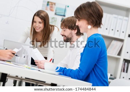Motivated young business team having a meeting sitting discussing and analyzing paperwork and reports - stock photo