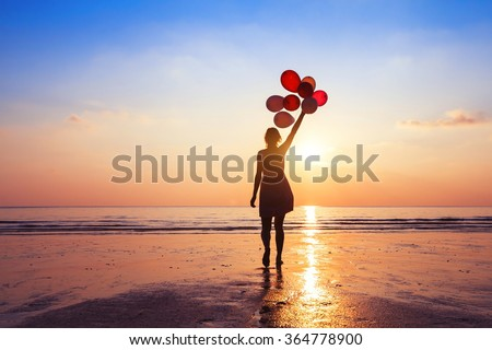 motivation or hope concept, follow your dream and inspiration, girl with balloons at sunset - stock photo
