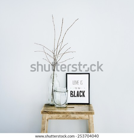Motivational frame LOVE IS THE NEW BLACK with glass bottles. Scandinavian hipster style room interior - stock photo