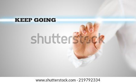 Motivational Image of Hand Touching Keep Going Statement on Touch Screen. - stock photo