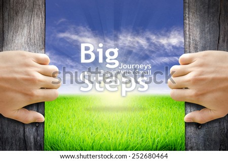 "Motivational quotes ""Big Journeys Begin With Small Steps"" . Hands opening a wooden door then found a texts floating among new world as green grass field, Blue sky and the Sunrise. - stock photo"