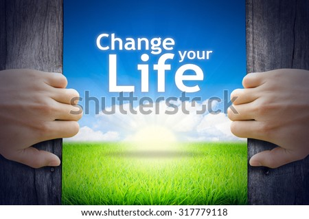 """Motivational quotes """"Change your Life"""". Hands opening a wooden door then found a texts floating among new world as green grass field, Blue sky and the Sunrise. - stock photo"""