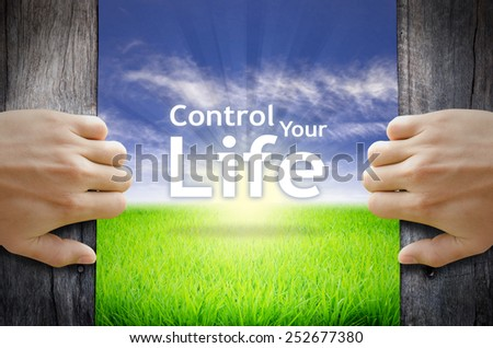 """Motivational quotes """"Control Your Life"""" . Hands opening a wooden door then found a texts floating among new world as green grass field, Blue sky and the Sunrise. - stock photo"""