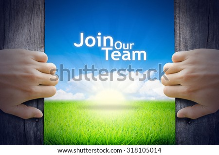 "Motivational quotes ""Join Our Team"". Hands opening a wooden door then found a texts floating among new world as green grass field, Blue sky and the Sunrise. - stock photo"