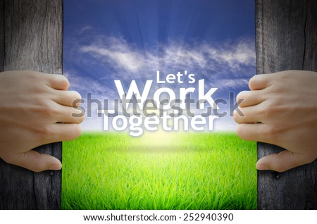 "Motivational quotes ""Let's work Together"" . Hands opening a wooden door then found a texts floating among new world as green grass field, Blue sky and the Sunrise. - stock photo"