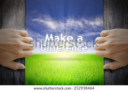 """Motivational quotes """"Make a Difference"""" . Hands opening a wooden door then found a texts floating among new world as green grass field, Blue sky and the Sunrise. - stock photo"""