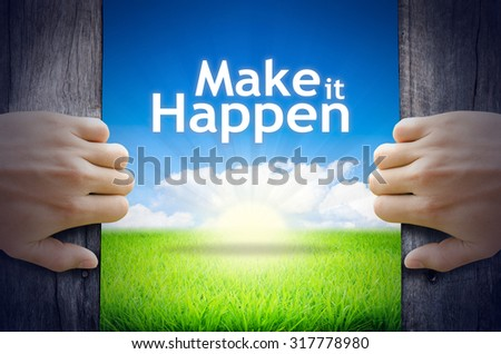 """Motivational quotes """"Make it Happen"""". Hands opening a wooden door then found a texts floating among new world as green grass field, Blue sky and the Sunrise. - stock photo"""
