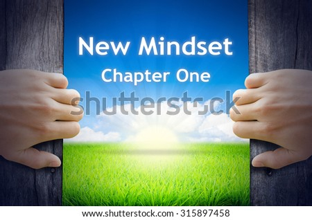 """Motivational quotes """"New Mindset Chapter One"""" . Hands opening a wooden door then found a texts floating among new world as green grass field, Blue sky and the Sunrise. - stock photo"""