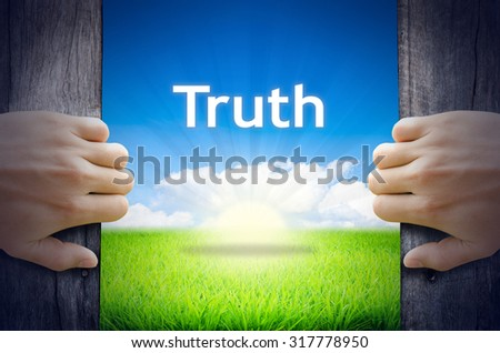 "Motivational quotes ""Truth"". Hands opening a wooden door then found a texts floating among new world as green grass field, Blue sky and the Sunrise. - stock photo"