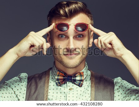 motive portrait of handsome young man in retro shirt, scottish in cell bow-tie and round unusual sunglasses posing over gray background. White shiny smile and healthy skin. Urban style. Studio shot