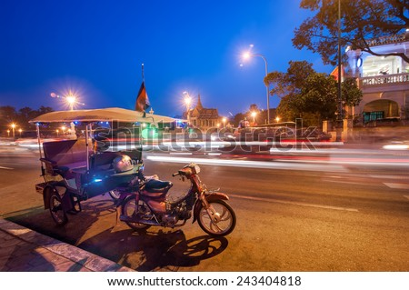 Moto taxi at asian city. Scene of night life at most popular tourist street near Mekong river in capital city Phnom Penh, Cambodia - stock photo