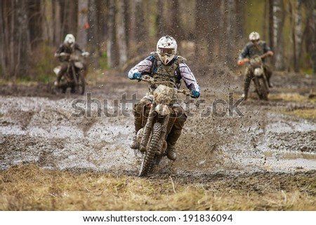Motocross driver on wet and muddy terrain in Finland. - stock photo