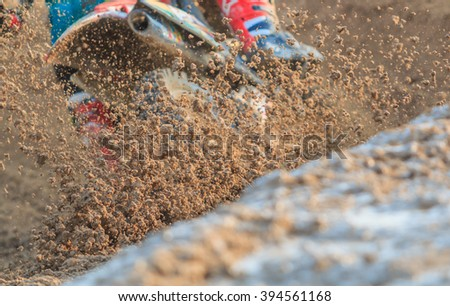 Motocross racer accelerating in dirt track, Details of debris in a motocross race and Picture blur