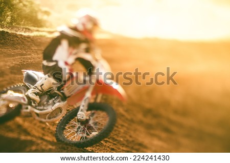 Motocross racer making a turn in dirt track - stock photo