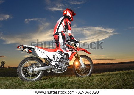 Motocross rider standing on motocycle during sunset  - stock photo