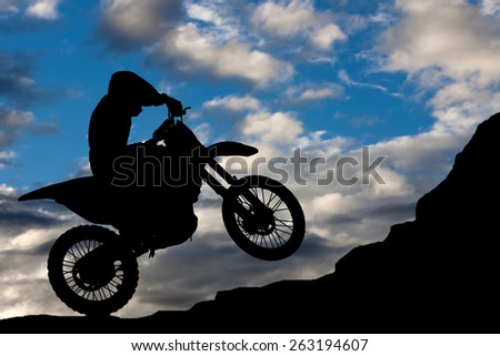 Motocross - silhouette with a rock and blue sky