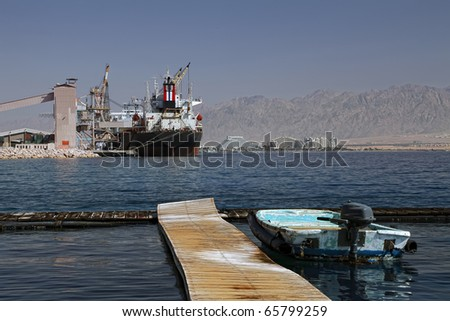Motor boat and the big transport ship on the Red sea