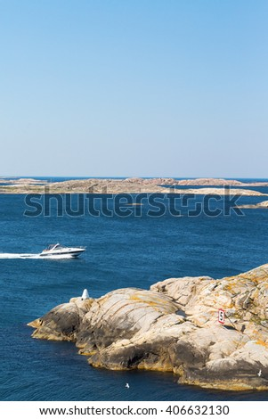 Motor boat in the archipelago with cliffs - stock photo