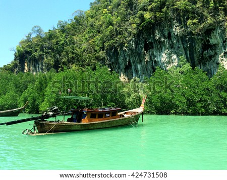Motor boat on the beach of Krabi Island,Thailand with mountain background.