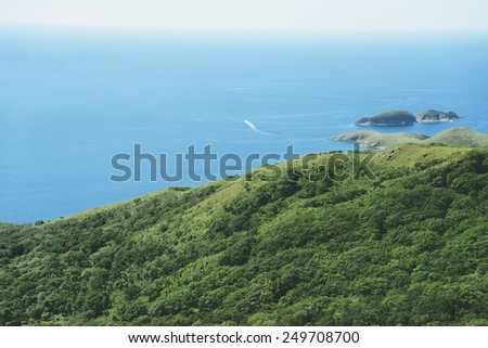 Motor boat sails on the sea from island in summer, top view - stock photo