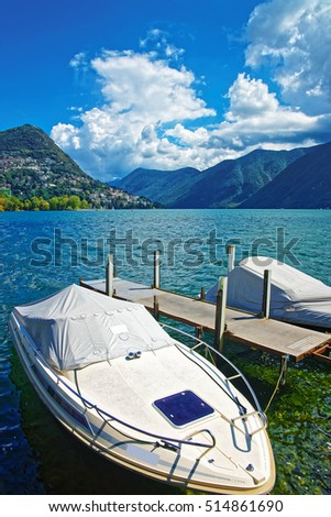 Motor Boats at the promenade of the luxurious resort in Lugano on Lake Lugano and Alps mountains, Ticino canton, Switzerland.