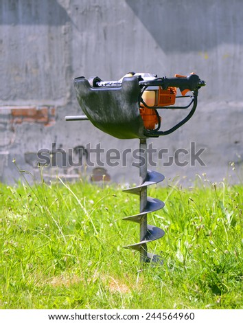Motor earth auger drilled in the earth. - stock photo