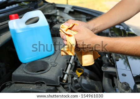 Motor mechanic cleaning his greasy hands after servicing car  - stock photo