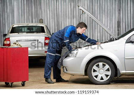 motor mechanic diagnosing automobile car engine before maintenance at repair service station - stock photo
