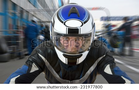 Motor racer leaving the pit during a race, accelerating from the pits lane, seen from the bike's perspective - stock photo