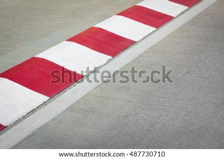 Motor racing circuit Red and White. White and red strip no Parking Sign on Footpath road. Road sign. Red and White sign on road. Motor race asphalt.  white and red of concrete road texture background.