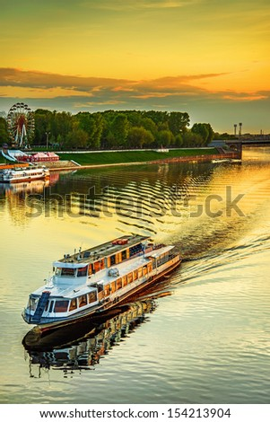 Motor ship at sunset sails on river Volga in Tver, Russia. - stock photo