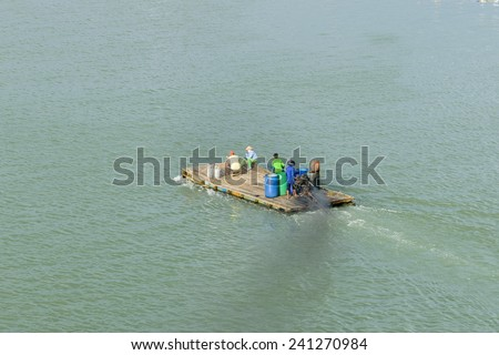 Motor Wooden raft crossing the river - stock photo
