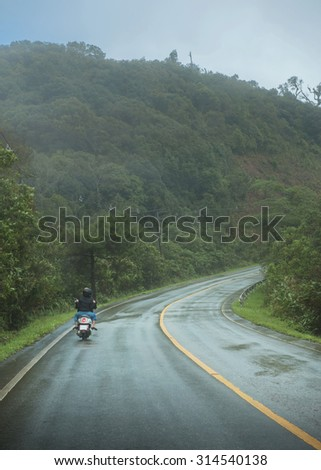 Motorbike on the country road in the foggy morning - stock photo