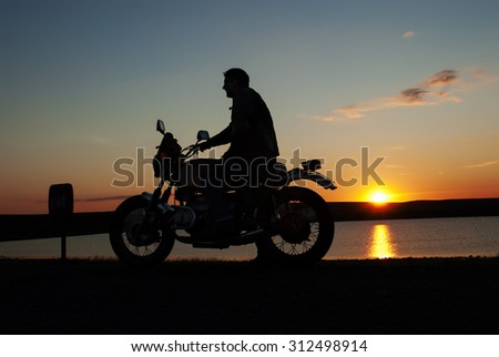 Motorbiker in silhouette at sunset by water man on motorbike one hand on handlebar
