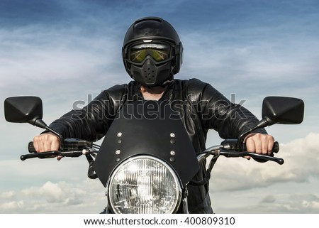 Motorbiker on motorbike with black helmet reflection of countryside in visor leather jacket blue sky white clouds with hands on handle bars stock photography