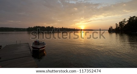 Motorboat at the dock with the sunset in the horizon in Lake of the Woods, Ontario - stock photo