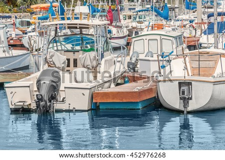 Motorboats tied to wooden dock at busy marina. Reflections in the calm water.  - stock photo