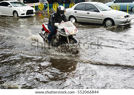 Motorcycle and cars on flooded road during the heavy rain