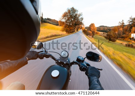 Motorcycle driver riding on motorway in beautiful sunset light. Shot from pillion driver view