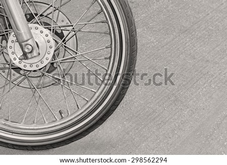 Motorcycle front tire side view close up, black and white photo. Slight drop shadow. Tread, brake, rotor, spokes detail. Blurred asphalt background. Copy space.  - stock photo