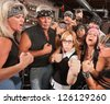 Motorcycle gang and female nerd holding up fists in bar - stock photo