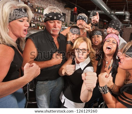 Motorcycle gang and female nerd holding up fists in bar