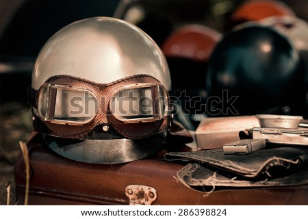 Motorcycle helmet with goggles and other retro objects. Vintage driver equipment - romantic travel on motorbike. - stock photo