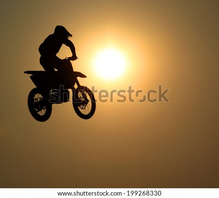 Motorcycle jumps in the air with sunset - stock photo