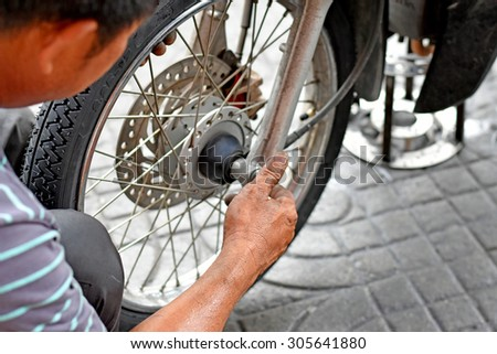 Motorcycle mechanic changing a wheel. - stock photo