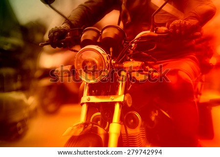 Motorcycle rider rushing at city street, colorized image - stock photo