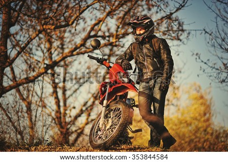 Motorcycle rider stay at sunset with him enduro bike - stock photo